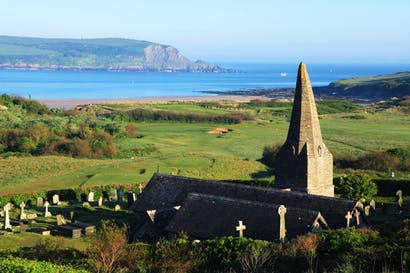 St Enodoc Church overlooking St Enodoc golf course and the sea beyond, Rock, Cornwall. John Betjeman lies buried in the graveyard