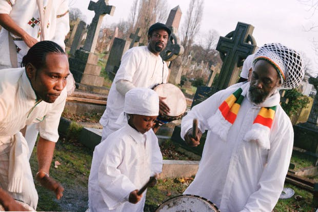 Drummers at a graveside wear white, based on Ethiopian orthodox funeral traditions
