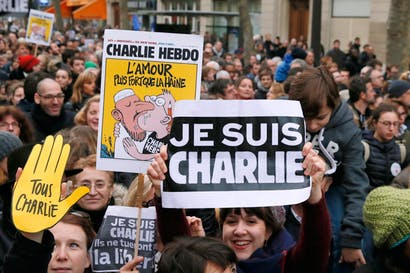 Demonstrators wave posters reading 'Je suis Charlie (I am Charlie)', during the Unity rally Marche Republicaine in Paris in tribute to the 17 victims of the Charlie Hebdo killing spreeby three Islamist terrorists.