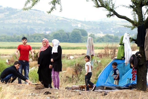Migrants warm up beside a campfire on the Macedonian-Greek border (Photo Robert Atanasovski/Getty)