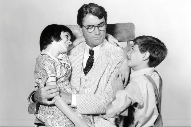 Atticus Finch (played by Gregory Peck) with his children Scout and Jem in the 1962 film version of To Kill a Mockingbird.