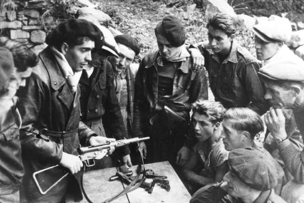 Members of the Maquis study the mechanism and maintenance of weapons dropped by parachute in the Haute-Loire