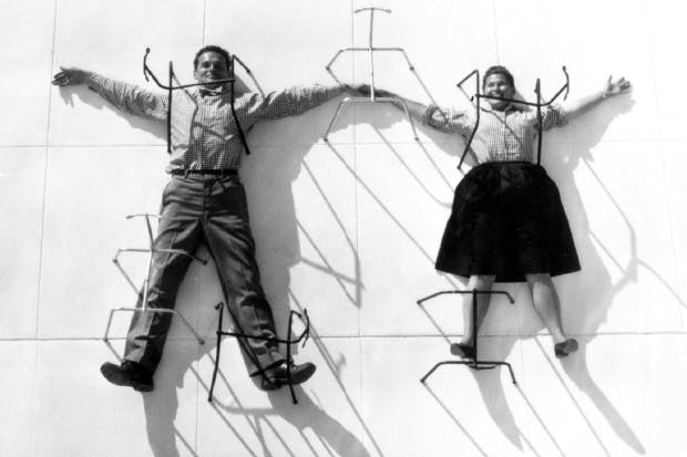 Hot seats: Charles and Ray Eames posing with chair bases