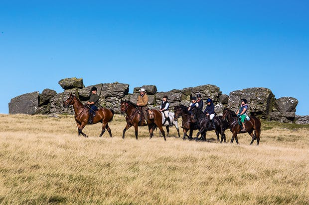 Stetson-clad Phil Heard leads riders on the moor