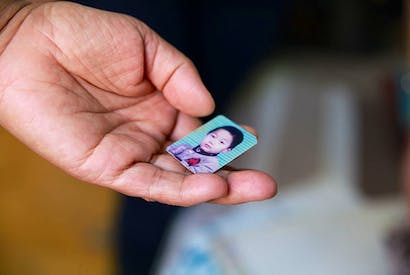 Small comfort: a mother, whose only son was killed in a car accident at the age of 23, holds a picture of him as a child. Many such bereaved parents, unable to conceive again and struggling to support themselves in later life, say they have nothing left to live for