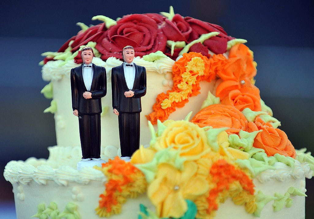 A wedding cake with statuettes of two me