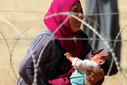 A mother and child, refugees from Raqqa, wait to cross into Turkey in September 2014