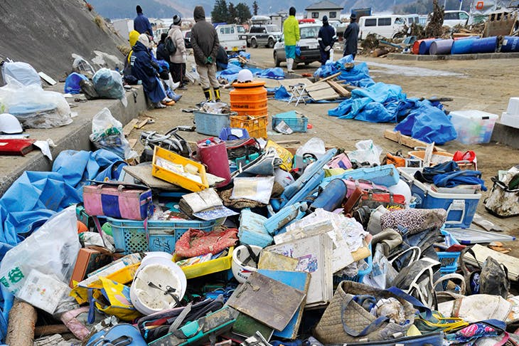 A pile of mud-covered satchels is all that remains of 74 children's lives