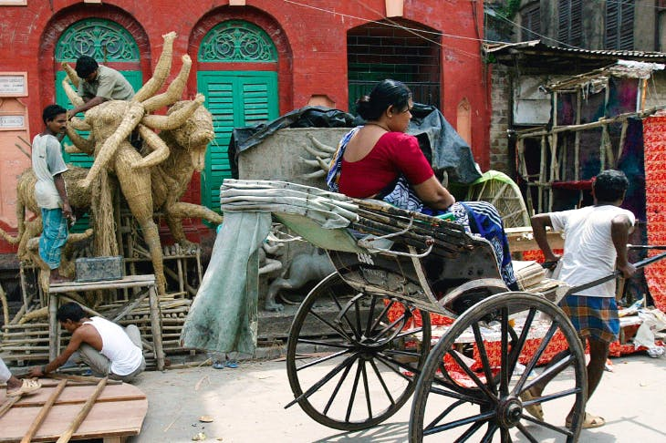 Deity sculptors work on a preliminary structure for the ten-armed Goddess Durga in preparation for the Durga Puja festival