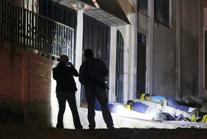 A nightly occurrence in Tegucigalpa. Forensic officers inspect a crime scene involving the execution of six men in drug-related gang warfare