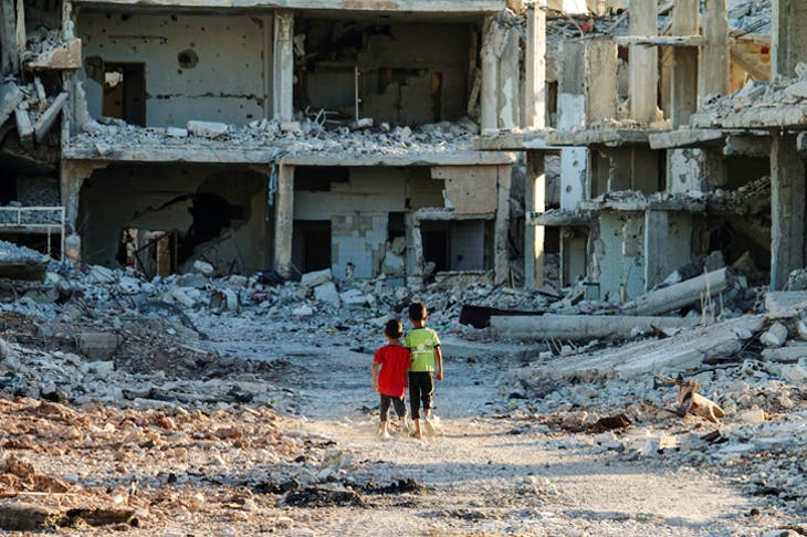 In rebel-held territory, two boys contemplate the rubble of Daraa, September 2017