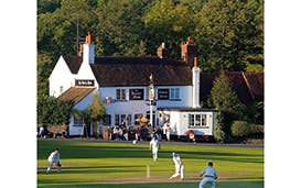 A game of cricket on Tilford Green, Surrey, outside The Barley Mow