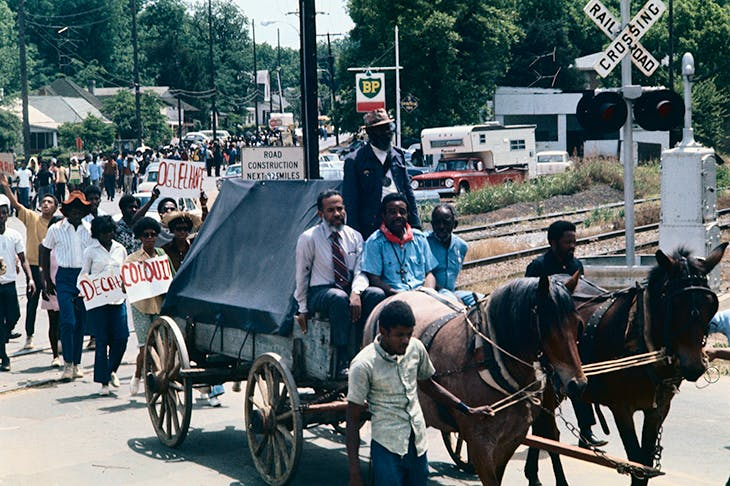 Ralph Abernathy (seated centre) and C.B. King (seated left) sit on a wagon as 300 protesters march to Atlanta. Photo: Getty/Bettmann