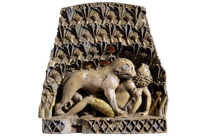 Ivory plaque of a lioness mauling a man, ivory, gold, cornelian, lapis lazuli, Nimrud, 900 BC–700 BC. [© The Trustees of the British Museum]