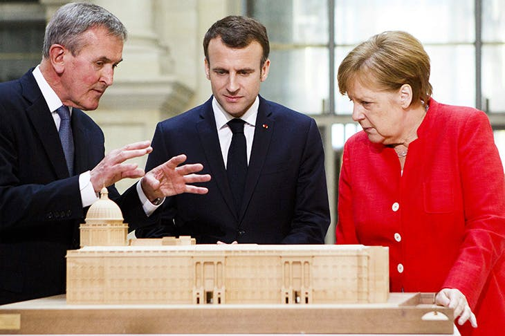Neil MacGregor shows German Chancellor Angela Merkel and French President Emmanuel Macron a model of the new Humboldt Forum. Photo: Carsten Koall / Getty Images