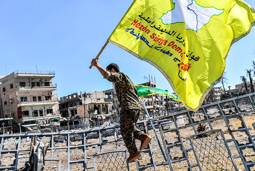 A member of the Syrian Democratic Forces holds up the group's flag (Getty)