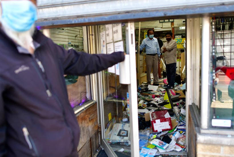 small Shop owners survey the damage to their store in Philadelphia, PA