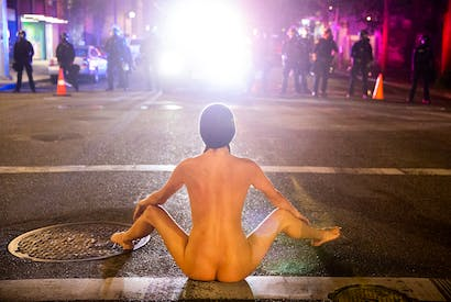 A naked protester sits in front of police