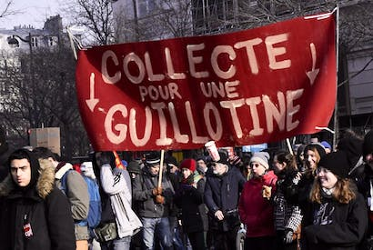 Protesters hold a banner reading ''Fund-raising for a guillotine'