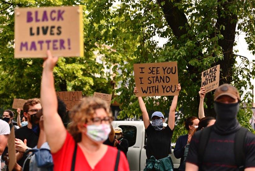 Protesters hold up signs on June 3, 2020